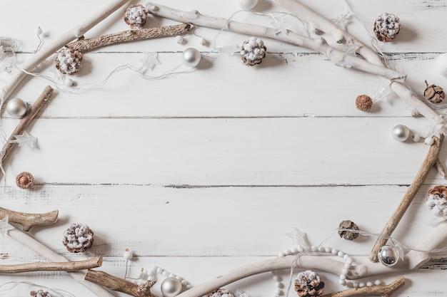 Draufsichtrahmen mit weihnachtsdekorationen auf weißem holz
