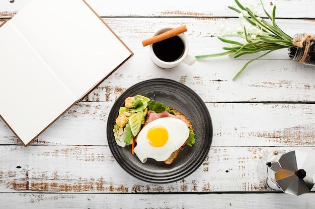 Draufsichtsatz des frühstückssandwiches nahe bei notizbuch