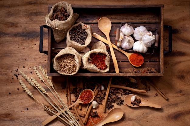 Draufsichtsatz gewürze und kräuter auf hölzernen behälter-, lebensmittel- und küchenbestandteilen.