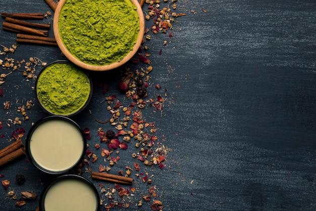 Draufsichtsatz pulverisierter grüner tee mit zimtstangen