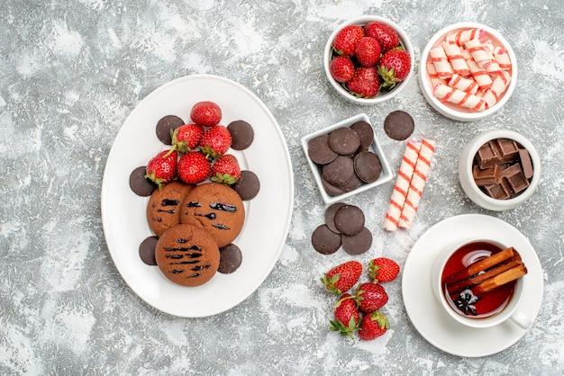 Draufsichtschalen mit bonbons erdbeerpralinen bonbons und einigen erdbeersüßigkeiten pralinen und einer tasse tee auf dem grauweißen grund