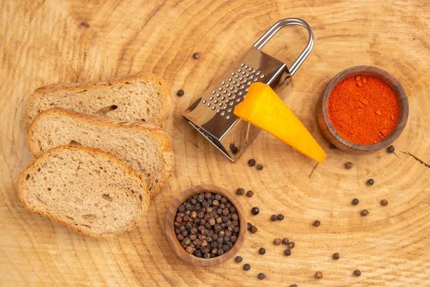 Draufsichtscheiben brot käsereibe verschiedene gewürze in kleinen schüsseln auf holztisch