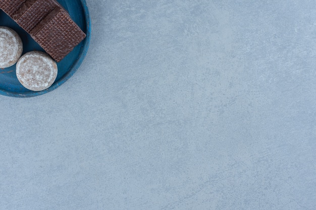 Draufsichtschokoladenwaffeln mit plätzchen auf blauer holzplatte.