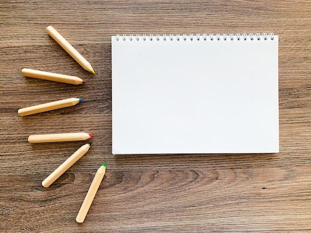 Draufsichtschreibtisch mit leerem notizbuch und bleistiften auf hölzerner tabelle