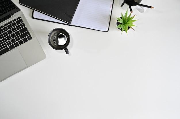 Draufsichtschreibtischlaptop-computer, kaffee, notizbuch mit bleistift auf weißer tabelle.
