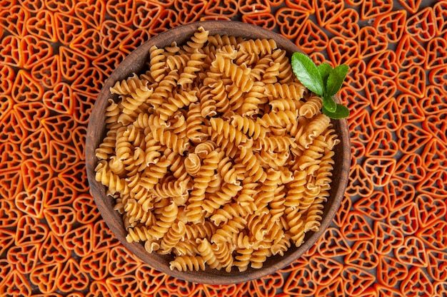 Draufsichtschüssel mit spirali-nudeln auf herzförmiger italienischer pasta auf dunklem tisch