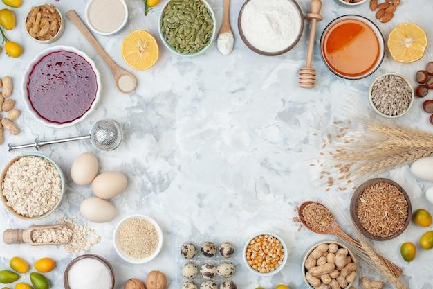 Draufsichtschüsseln mit verschiedenen müsli-honig-stick-holzlöffeln-eiern cumcuats auf dem tisch mit kopienplatz