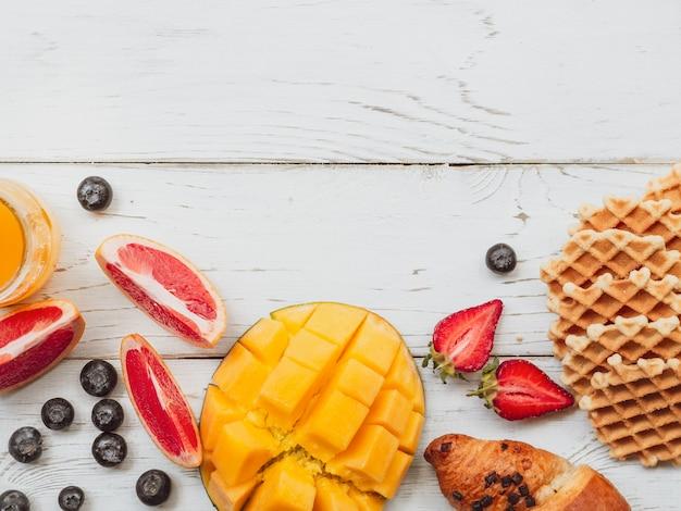 Draufsichtsommerfrühstück mit waffel und früchten.