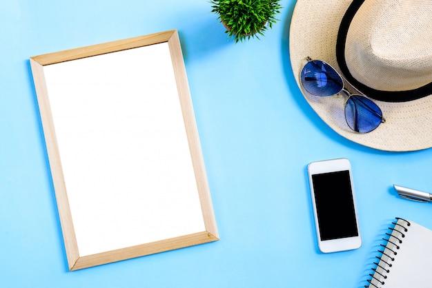 Draufsichtsommerreise-planungskonzept mit weißem hut, blauen brillen, telefon, notizbuch