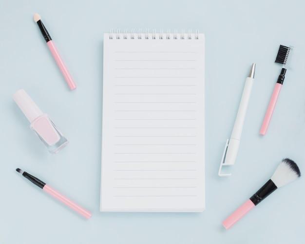 Draufsichtsortiment mit make-upbürsten und notizbuch