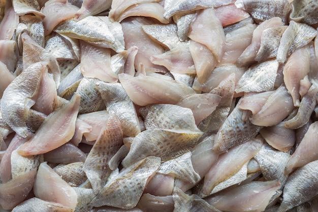 Draufsichtstapel geschnittener roher, frischer fisch, nachdem er filetiert worden ist. essen hintergrund