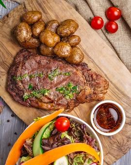 Draufsichtsteak mit kartoffeln und soße auf dem brett mit salat und gemüse