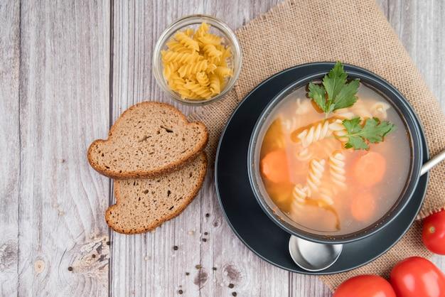 Draufsichtsuppe in schüssel mit brot und tomaten