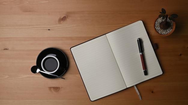 Draufsichttasse kaffee, kaktus und notizbuch auf hölzernem schreibtisch.