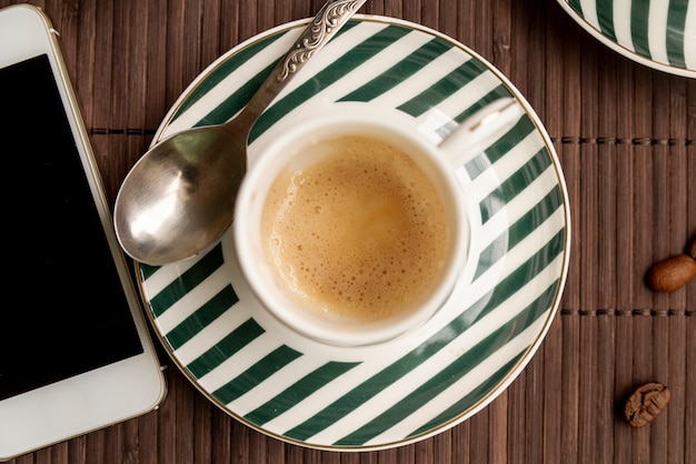 Draufsichttasse kaffee mit einem smartphone