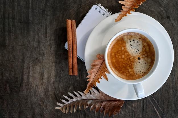 Draufsichttasse kaffee mit trockenem blatt auf hölzernem.