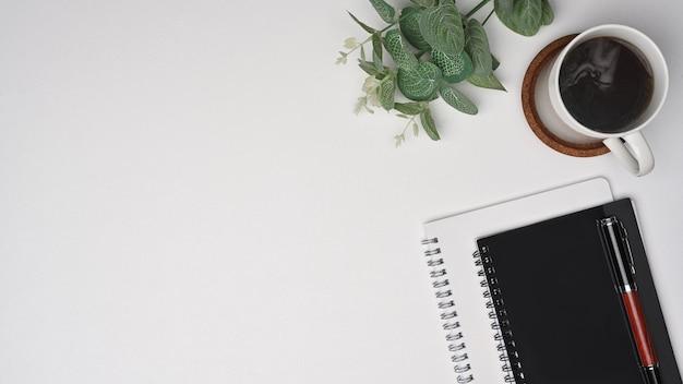 Draufsichttasse kaffee und notizbuch auf weißem hintergrund.