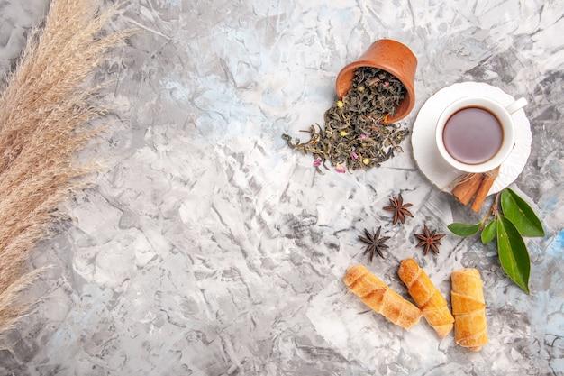 Draufsichttasse tee mit bagels auf weißem tischteekuchengebäckkuchen