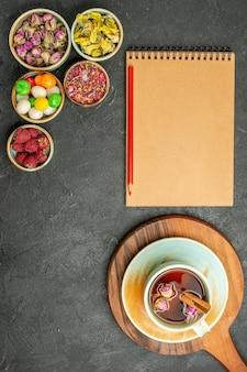 Draufsichttasse tee mit blumen und bonbons auf dem grauen raum