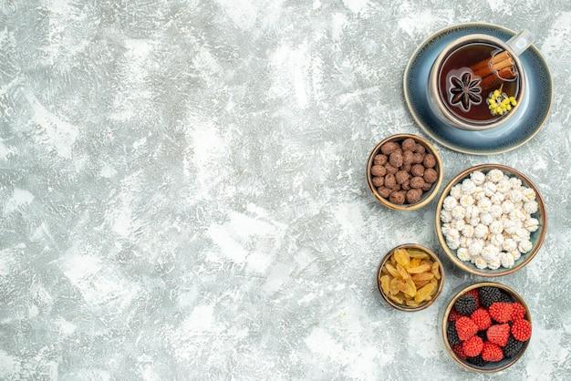 Draufsichttasse tee mit bonbons auf weißem raum
