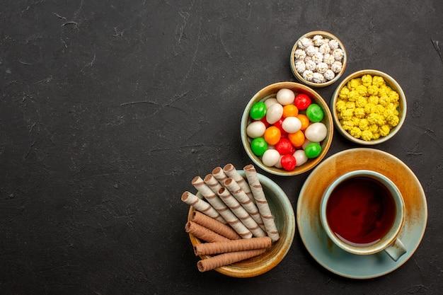 Draufsichttasse tee mit bonbons und keksen auf dunklem raum