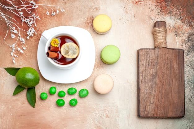 Draufsichttasse tee mit bonbons und macarons auf hellem schreibtischtee-zitronenkeks