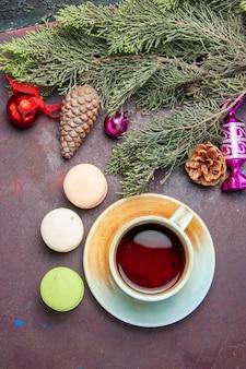Draufsichttasse tee mit französischen macarons auf dunklem hintergrundkuchenkeks-zuckerkuchen