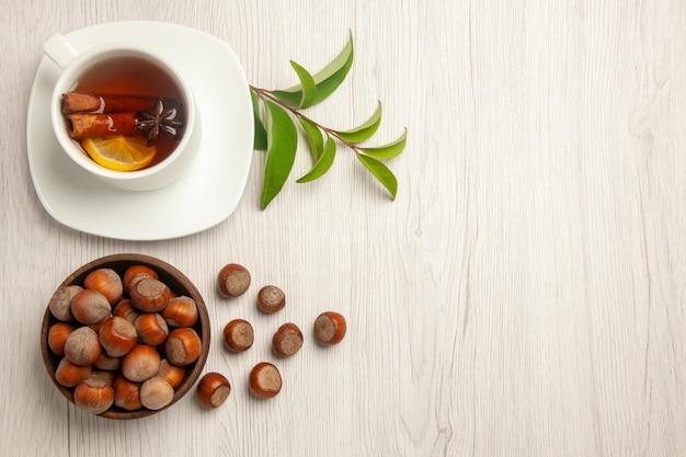 Draufsichttasse tee mit frischen haselnüssen auf weißer schreibtischtee-nuss-snackzeremonie