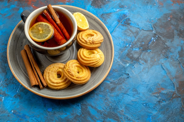 Draufsichttasse tee mit keksen auf blauem tischbiskuit-süßigkeit-tee-plätzchen