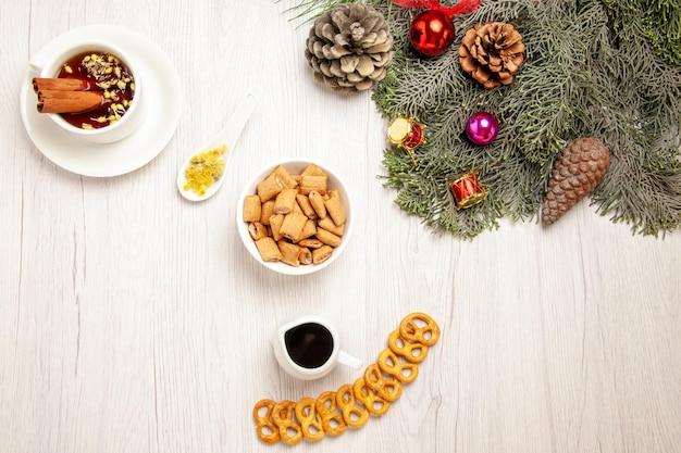 Draufsichttasse tee mit keksen und baum auf weißem raum