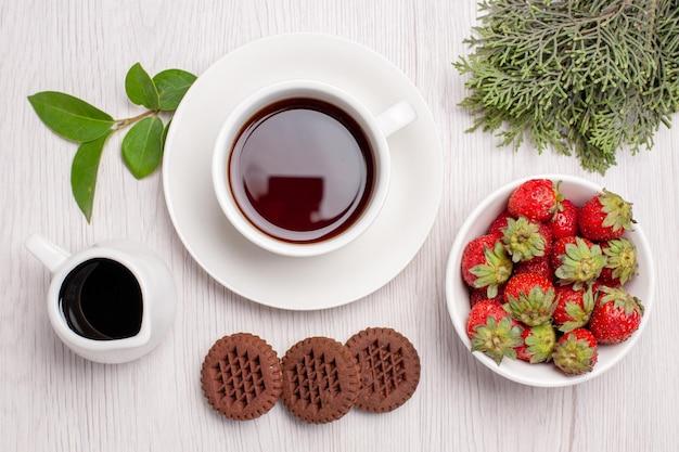 Draufsichttasse tee mit keksen und erdbeeren auf weißem schreibtisch zuckerteeplätzchen keks süß