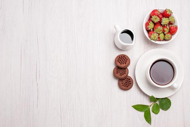 Draufsichttasse tee mit keksen und erdbeeren auf weißem schreibtisch zuckerteeplätzchen süßer keks