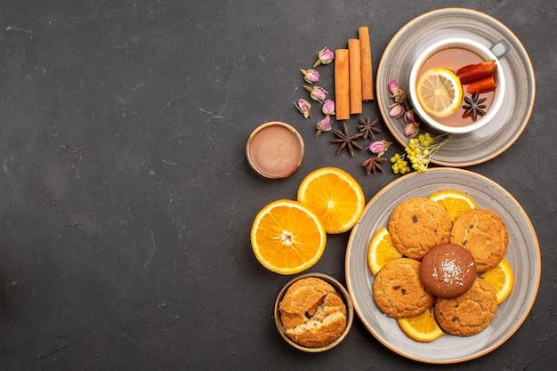 Draufsichttasse tee mit keksen und frisch geschnittenen orangen auf der dunklen oberfläche süßer teefruchtkeksplätzchen