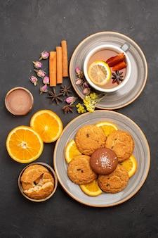 Draufsichttasse tee mit keksen und frisch geschnittenen orangen auf dunkler oberfläche tee zuckerfruchtkeks süßer keks