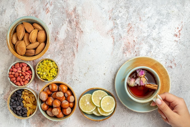 Draufsichttasse tee mit rosinennüssen und zitronenscheiben auf weißer oberfläche fruchttee zitrusgetränk Kostenlose Fotos