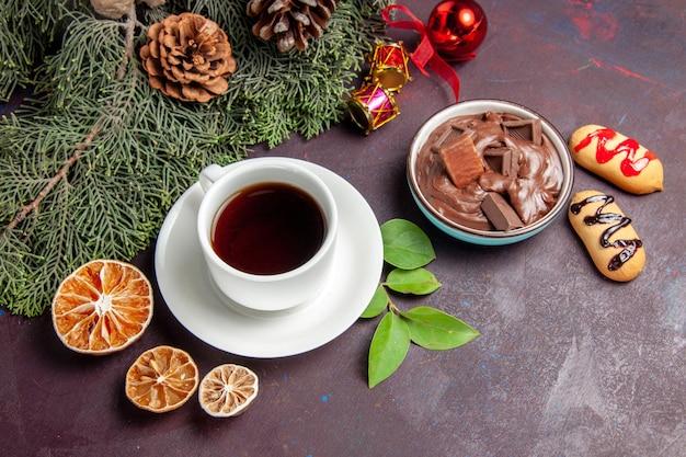 Draufsichttasse tee mit schokoladendessert und keksen auf dunklem raum