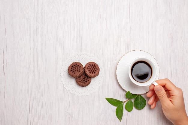 Draufsichttasse tee mit schokoladenkeksen auf dem weißen schreibtisch zuckerteeplätzchen süßer keks