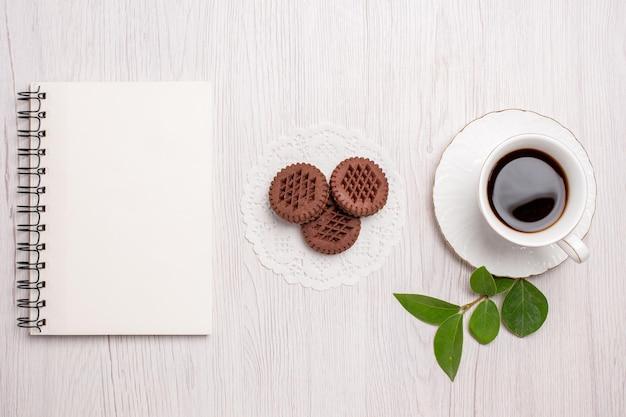 Draufsichttasse tee mit schokoladenkeksen auf weißem schreibtisch zuckerteeplätzchen süßer keks
