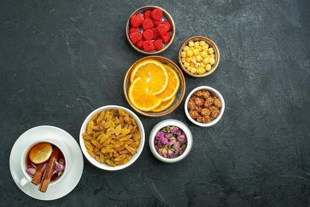Draufsichttasse tee mit süßigkeiten nüssen und orangenscheiben auf dunkler oberfläche konfitüre tee süßigkeiten süß