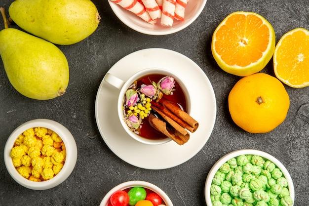 Draufsichttasse tee mit süßigkeiten und frischen früchten auf grauem raum