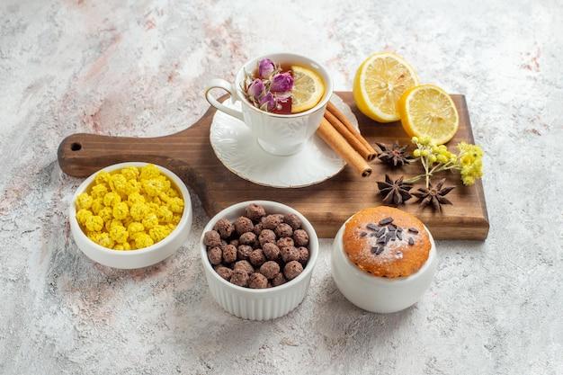 Draufsichttasse tee mit süßigkeiten und zitronenscheiben auf weißem raum