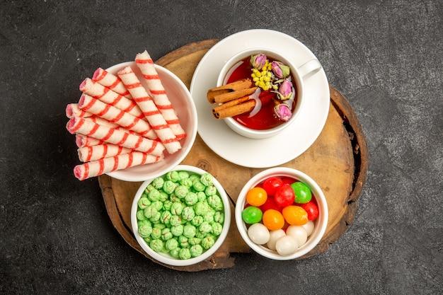 Draufsichttasse tee mit verschiedenen bonbons auf grauem schreibtisch teefarbe regenbogen süße süßigkeiten