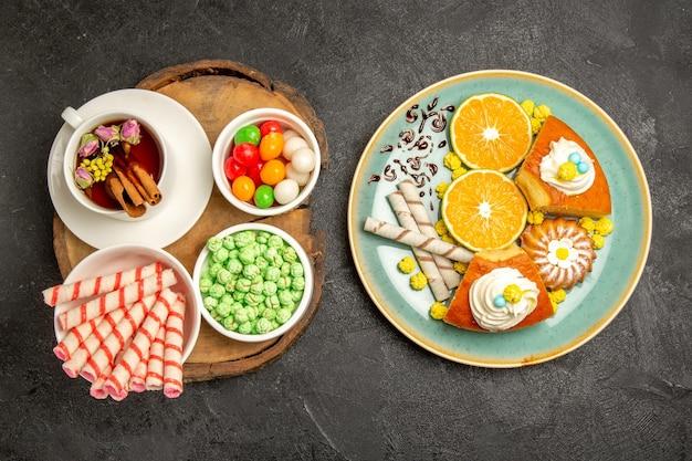 Draufsichttasse tee mit verschiedenen bonbons und kuchenscheiben auf dunkelgrauem raum