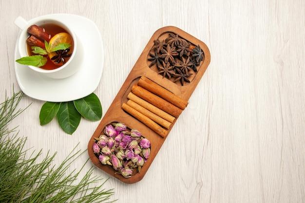 Draufsichttasse tee mit zimt und blumen auf weißer schreibtischteefarbgeschmackblume