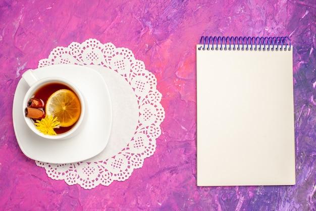 Draufsichttasse tee mit zitrone und zimt auf dem rosa tischbonbonfarbenen tee