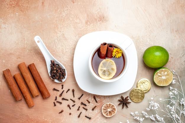 Draufsichttasse tee mit zitrone und zimt auf hellbraunem tischzitronenkekstee
