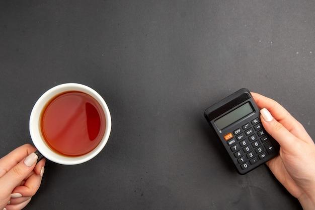 Draufsichttasse tee und taschenrechner in weiblichen händen auf dunklem tisch