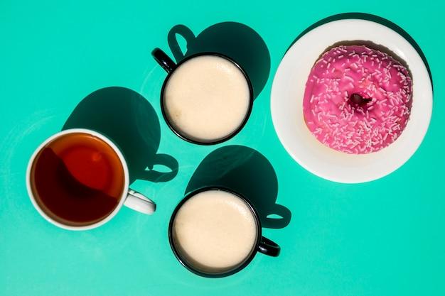 Draufsichttassen kaffee mit doghnut