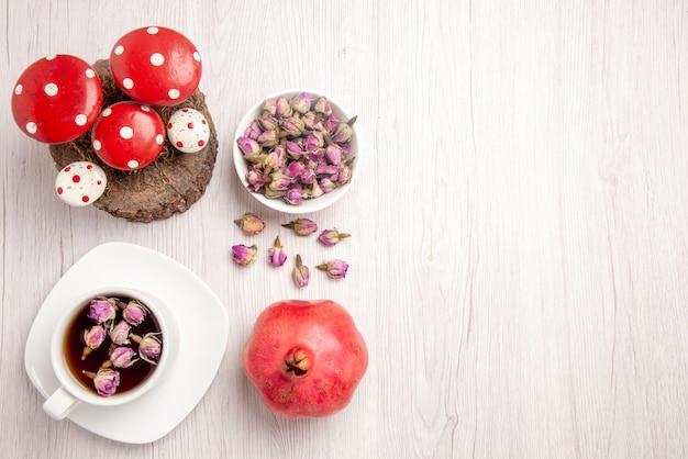 Draufsichttee und granatapfel eine tasse kräutertee auf der weißen untertasse neben den granatapfelkräutern und weihnachtsspielzeug auf dem tisch