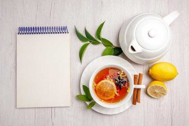 Draufsichttee und zimt eine tasse kräutertee-zimtstangen auf der untertasse neben der weißen notizbuch-zitronen-teekanne und blätter auf dem weißen tisch